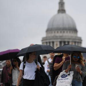 Ihmisiä sateenvarjon alla Lontoossa.