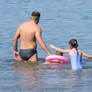 Isä ja lapsi kahlaavat vedessä, isä vetää toista lasta uimarenkaassa.