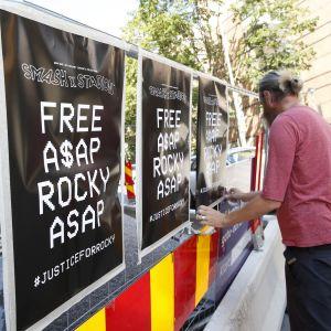 Mies kiinnittää julistetta, jossa vaaditaan räppärin vapauttamista.
