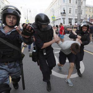 Kaksi mellakkavarusteisiin pukeutunutta poliisia kuljettaa vaaleanharmaaseen t-paitaan ja mustiin shortseihin pukeutunutta miestä kadulla. He pitävät miehen käsiä ylhäällä selän takana. Kolmas poliisimies kulkee edellä ja ojentaa kättään kohti kameraa.