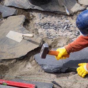 Mies laittaa kivilaatoitusta pihaan.