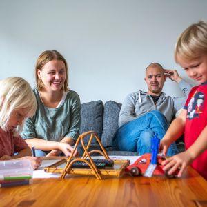 Perhe viettää yhdessä aikaa olohuoneessa.