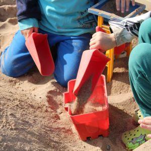 Kaksi lasta leikkii hiekkalaatikolla.