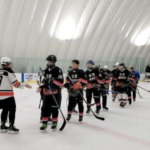 Kaksi jääkiekkojoukkuetta kättelee.
