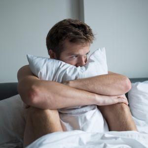mies rutistaa tyynyä sängyllä