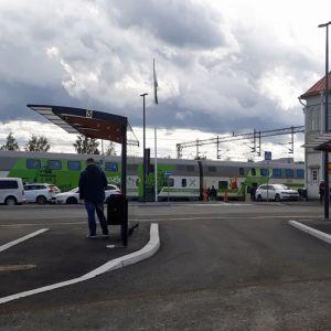 Matkakeskuksen pihalla on junaa ja linja-autoa odottavia ihmisiä.