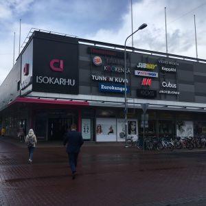 Kauppakeskus Isokarhu sijaitsee Porissa kävelykadulla. Kesän lopulla otettu kuva on otettu puolipilvisenä päivänä sateen jälkeen vuonna 2019. Kuvassa muutama ihminen kävelle kohti kauppakeskuksen sisäänkäyntiä.