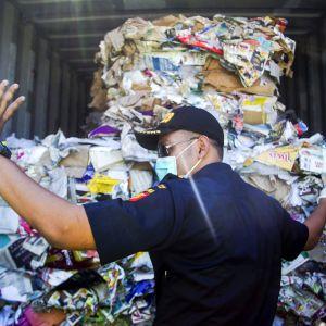 Tullivirkailija tarkistaa Australiasta tuotua roskakonttia.