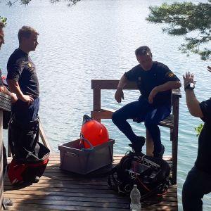 Pelastuslaitoksen miehiä järven rannalla.