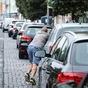Mies työntää autoaan jonossa bensa-asemalle