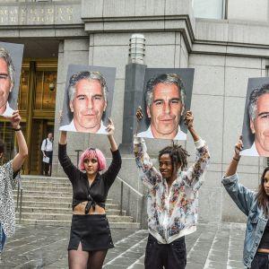 Neljä naista pitelee kylttejä joissa on Jeffrey Epsteinin kuva oikeustalon edessä.