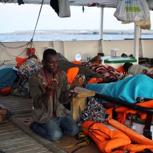 Libyan edustalta pelastettu siirtolainen rukoilee Open Arms -pelastusaluksella.