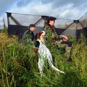 Mies, nainen ja kaksi koiraa sorsapassissa.