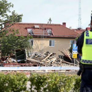 Poliisi katsoo räjäytettyä rakennusta.