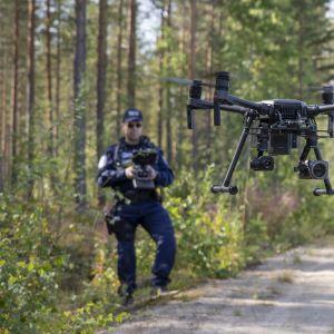 Poliisi lennättää droonia.