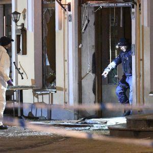 Poliisin tutkijat räjähdyksessä vaurioituneen ravintolan edustalla.