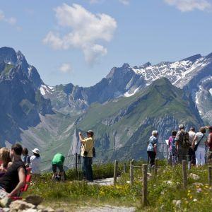 Turisteja kesäisessä alppimaisemassa.