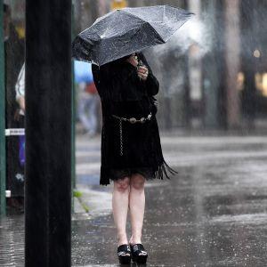 Nainen polttaa sähkötupakkaa sateenvarjon alla sateessa Helsingissä
