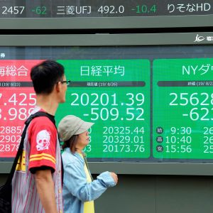 Ohikulkijat katselevat Tokion, Shanghain ja New Yorkin pörssien indeksejä infotauluilta Tokion pörssin edustalla.