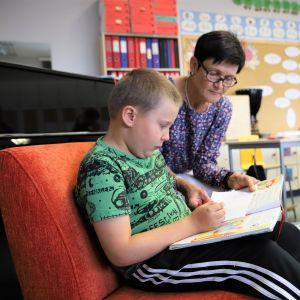 Luokanopettaja Heini Ylisuutari kuuntelee kun Johannes Rantala lukee