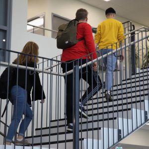 Oppilaat kävelevät ylös portaita.