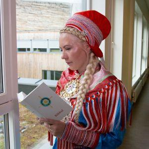 Nainen lukee pohjoissaameksi käännettyä Raamattua, Biibbalia.