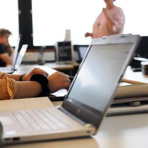 Kannettavia tietokoneita pöydällä, oppilaat kuuntelevat opettajaa.