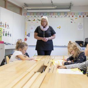 Nainen opettaa kolmea lasta luokassa.