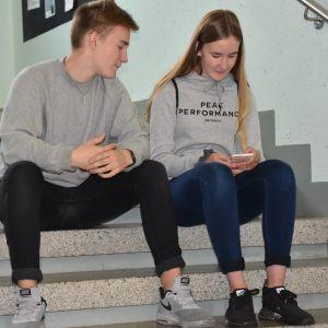 Elias Tanninen ja Kiia Kulosaari istuvat koulun portailla ja katselevat kännykkää.