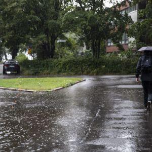 Jalankulkija sateenvarjon kanssa Helsingin Lauttasaaressa.