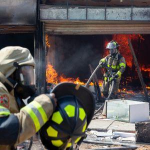 Palomiehet sammuttavat palavaa liikettä.
