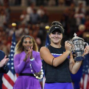 Bianca Andreescu poseeraa mestaruuspystin kanssa, Serena Williams taustalla.