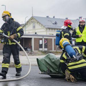 Palomies on juuri huuhdellut harjoituspotilaan, joka on istuvilteen paareilla, suoja-asu päällään.