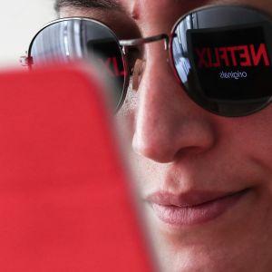 Netflix-logo heijastuu läppärin näytöltä naisen aurinkolaseihin.