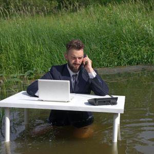 Mies puhuu puhelimeen työpöydän ääressä rantavedessä, kaislikon edessä,