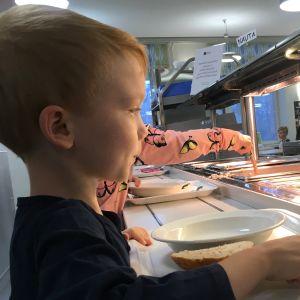 Poika koulun ruokalan linjastolla ottamassa aamupalaa.