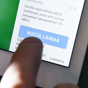 Henkilö käyttää älypuhelinta nostaakseen lainaa.