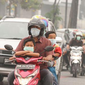 Hengityssuojaimia käyttäviä moottoripyöräilijöitä.