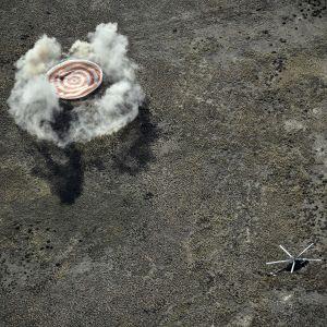 Pölypilvi nousee maasta paluukapselin laskeuduttua laskuvarjon avustamana.