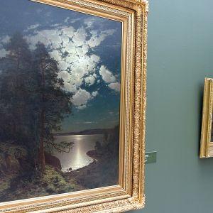 Kaksi Hjalmar Munsterhjelmin kuutamoaiheista taulua taidemuseon seinällä