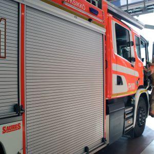 Palomies kiipeää paloautoon.