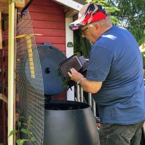 Jarkko Väisänen tyhjentämässä biojäteastiaansa kompostiin