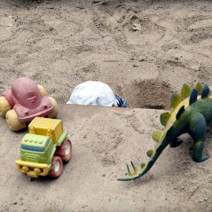Hiekkalaatikolla leikkivä yksinäinen, lähes piiloutunut lapsi.