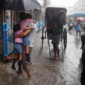 Mies kantoi lapsiaan kouluun tulvivassa Kolkatassa 25. syyskuuta.