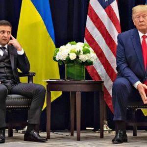 Ukrainan presidentti Volodymyr Zelenskyi vilkaisee hieman epäluuloisesti selkä suorana seisovaa Donald Trumpia.