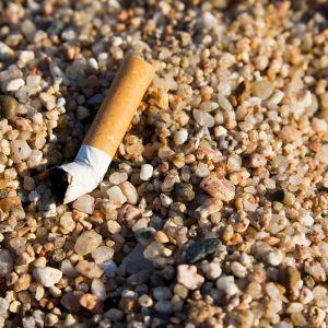Tupakantumppi rantahiekassa.