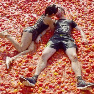 Pariskunta suutelee tomaattien päällä tomaattisota-festivaalilla Venäjällä.