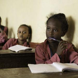 Pikkutyttöjä istuu luokassa.