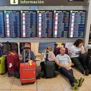 Matkustajat istuvat El Pratin lentoaseman lattialla.