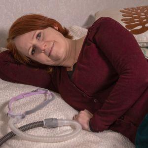 Hanna Tuovila makaa sängyllä vierellään uniapneamaski.